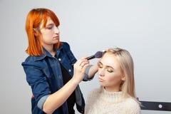 Ξανθού κοριτσιού με τις ιδιαίτερες προσοχές και το ασιατικό ύφος makeup στα βλέφαρα σε ένα στούντιο ομορφιάς σε ένα άσπρο υπόβαθρ στοκ εικόνες