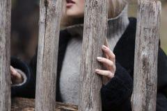 Ξανθός έφηβος που στέκεται πίσω από τον ξύλινο φράκτη Στοκ εικόνα με δικαίωμα ελεύθερης χρήσης