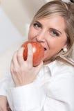 Ξανθός δαγκώνοντας ένα μήλο στοκ φωτογραφία