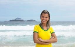 Ξανθός βραζιλιάνος αθλητικός ανεμιστήρας με τα διασχισμένα όπλα στην παραλία Στοκ φωτογραφία με δικαίωμα ελεύθερης χρήσης