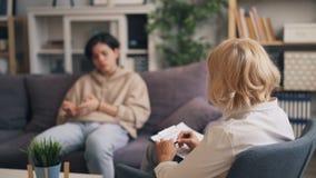 Ξανθός επαγγελματικός ψυχολόγος γυναικών που συμβουλεύεται το δυστυχισμένο έφηβο στην κλινική απόθεμα βίντεο