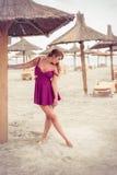 Ξανθός ευτυχής μόδας στην τοποθέτηση θάλασσας shoe-less στην άμμο στοκ εικόνες με δικαίωμα ελεύθερης χρήσης