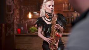 Ξανθός θηλυκός μουσικός που εκτελεί παθιασμένα ένα τραγούδι σε ένα saxophone απόθεμα βίντεο