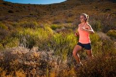 Ξανθός θηλυκός δρομέας ιχνών που τρέχει μέσω ενός τοπίου βουνών Στοκ φωτογραφία με δικαίωμα ελεύθερης χρήσης