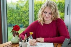 Ξανθός καλλιτέχνης γυναικών που σύρει και που σκιαγραφεί Στοκ Φωτογραφία