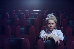 Ξανθός κινηματογράφος προσοχής κοριτσιών στο κενό θέατρο Στοκ Εικόνες
