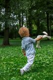 Ξανθός λίγο αγόρι παιδιών που παίζει το πράσινο πάρκο Στοκ Εικόνα
