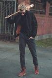 Ξανθός μαλλιαρός χούλιγκαν με το ρόπαλο του μπέιζμπολ Στοκ Εικόνες