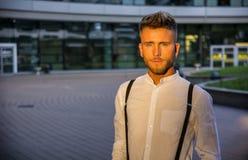 Ξανθός νεαρός άνδρας δίπλα στο σύγχρονο κτήριο στην πόλη Στοκ Εικόνα