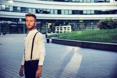 Ξανθός νεαρός άνδρας δίπλα στο σύγχρονο κτήριο στην πόλη Στοκ Φωτογραφία