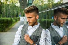 Ξανθός νεαρός άνδρας δίπλα στο σύγχρονο κτήριο στην πόλη Στοκ φωτογραφία με δικαίωμα ελεύθερης χρήσης