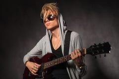 Ξανθός νεαρός άνδρας με την ακατάστατη κιθάρα παιχνιδιού τρίχας στο στούντιο Στοκ εικόνα με δικαίωμα ελεύθερης χρήσης