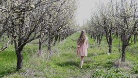 Ξανθός σε έναν ανθίζοντας κήπο και απολαύστε τη μυρωδιά φιλμ μικρού μήκους