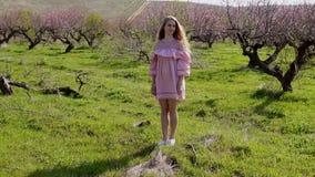 Ξανθός σε έναν ανθίζοντας κήπο και απολαύστε τις μυρωδιές απόθεμα βίντεο