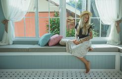 Ξανθός σε ένα καπέλο αχύρου κάθεται στον καναπέ από το παράθυρο η εικόνα ενός σύγχρονου κοριτσιού Πρότυπο με τις δερματοστιξίες Στοκ Φωτογραφία