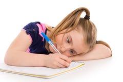 Ξανθός σπουδαστής κοριτσιών παιδιών με το σπειροειδές σημειωματάριο στο γραφείο Στοκ Εικόνα