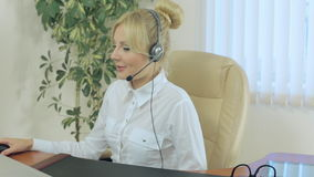 Ξανθός στα ακουστικά επικοινωνήστε με τους πελάτες επάνω φιλμ μικρού μήκους