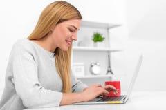 Ξανθός στο γραφείο της στο σπίτι ή στο γραφείο με ένα lap-top και ένα κόκκινο φλυτζάνι Στοκ εικόνες με δικαίωμα ελεύθερης χρήσης