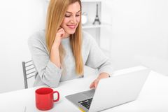 Ξανθός στο γραφείο της στο σπίτι ή στο γραφείο με ένα lap-top και ένα κόκκινο φλυτζάνι Στοκ Φωτογραφία