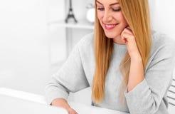 Ξανθός στο γραφείο της στο σπίτι ή στο γραφείο με ένα lap-top και ένα κόκκινο φλυτζάνι Στοκ Εικόνες