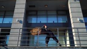 Ξανθός χορευτής οδών γυναικών που αποδίδει κοντά στα κιγκλιδώματα μετάλλων του σύγχρονου κτηρίου φιλμ μικρού μήκους