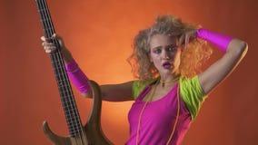 Ξανθός χορευτής disco της δεκαετίας του '80, που θέτει με την κιθάρα, πορτοκαλί υπόβαθρο απόθεμα βίντεο