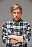 0 ξανθός όμορφος νεαρός άνδρας που φορά το περιστασιακό πουκάμισο καρό με τα χέρια που διασχίζονται στο στήθος που εξετάζει τη κά Στοκ Εικόνες