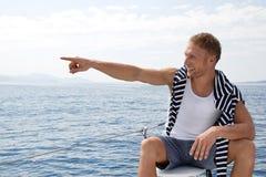 Ξανθός όμορφος νεαρός άνδρας σε μια πλέοντας βάρκα που δείχνει σε κάτι Στοκ φωτογραφίες με δικαίωμα ελεύθερης χρήσης