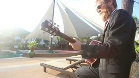 ξανθό άτομο στο μαύρες κοστούμι και την κιθάρα παιχνιδιών γυαλιών ηλίου απόθεμα βίντεο