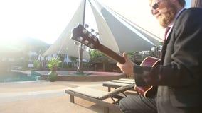 Ξανθό άτομο στο μαύρες κοστούμι και την κιθάρα παιχνιδιών γυαλιών ηλίου φιλμ μικρού μήκους