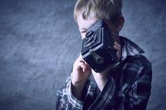 Ξανθό αγόρι παιδιών με την εκλεκτής ποιότητας κάμερα ταινιών φωτογραφιών στοκ εικόνες