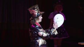 Ξανθό βιολί παιχνιδιού κοριτσιών στο φόρεμα βραδιού Αρσενικός μάγος που παρουσιάζει τέχνασμα με τη μετατροπή του μπαλονιού στο λε φιλμ μικρού μήκους