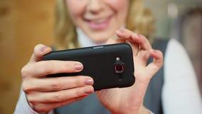 Ξανθό θηλυκό παιχνίδι στο smartphone της στην εργασία Σύγχρονες τεχνολογίες και συσκευές απόθεμα βίντεο