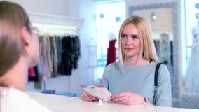 Ξανθό θηλυκό που παίρνει τις πληροφορίες ένας σύμβουλος στο γραφείο της μπουτίκ φορεμάτων πολυτέλειας απόθεμα βίντεο