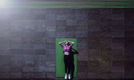 Ξανθό θηλυκό που πηδά επάνω, στο μοντέρνο κλίμα πορτών πρασινάδων, υπαίθριο Στοκ εικόνες με δικαίωμα ελεύθερης χρήσης