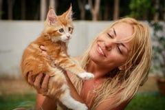 Ξανθό κορίτσι και κόκκινο γατάκι κοντά στο σπίτι Στοκ φωτογραφία με δικαίωμα ελεύθερης χρήσης