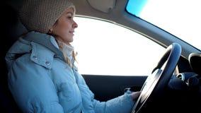 Ξανθό κορίτσι καμπινών αυτοκινήτων στις πλεκτές κινήσεις καπέλων τη χειμερινή ημέρα απόθεμα βίντεο
