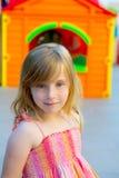 Ξανθό κορίτσι κατσικιών που χαμογελά στην υπαίθρια παιδική χαρά Στοκ Εικόνες