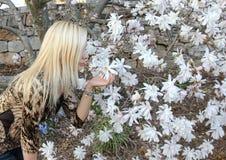 ξανθό κορίτσι λουλουδιών που μυρίζει το λευκό του ST Στοκ Εικόνα