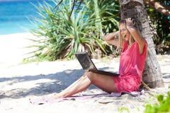 Ξανθό κορίτσι με ένα lap-top στην τροπική παραλία Στοκ Φωτογραφίες