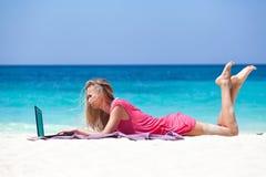Ξανθό κορίτσι με ένα lap-top στην τροπική παραλία Στοκ εικόνα με δικαίωμα ελεύθερης χρήσης