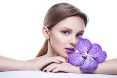 Ξανθό κορίτσι με τα ιώδη χείλια και λουλούδι που απομονώνεται Στοκ Εικόνες