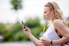 Ξανθό κορίτσι με την κινητή τηλεφωνική συνεδρίαση στον πάγκο Στοκ εικόνες με δικαίωμα ελεύθερης χρήσης