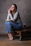 Ξανθό κορίτσι με το βιβλίο και το ποτήρι του κρασιού Γκρίζα ανασκόπηση Στοκ Εικόνες