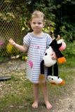 Ξανθό κορίτσι μικρών παιδιών στα γυμνά πόδια θερινών φορεμάτων με το παιχνίδι αγελάδων Στοκ φωτογραφίες με δικαίωμα ελεύθερης χρήσης