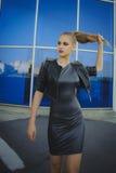 Ξανθό κορίτσι μόδας στο μπλε υπόβαθρο υπαίθριο με την ομαλή τρίχα Στοκ Εικόνες