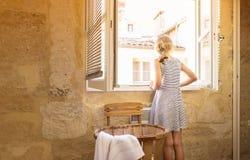 Ξανθό κορίτσι παιδιών σε ένα φόρεμα που φαίνεται έξω το παράθυρο Στοκ φωτογραφίες με δικαίωμα ελεύθερης χρήσης