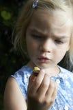 Ξανθό κορίτσι παιδιών που παρουσιάζει και που μελετά λίγο νέο σαλιγκάρι Στοκ εικόνα με δικαίωμα ελεύθερης χρήσης