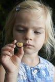 Ξανθό κορίτσι παιδιών που παρουσιάζει και που μελετά λίγο νέο σαλιγκάρι Στοκ Εικόνα