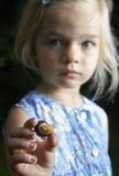 Ξανθό κορίτσι παιδιών που παρουσιάζει και που μελετά λίγο νέο σαλιγκάρι Στοκ εικόνες με δικαίωμα ελεύθερης χρήσης